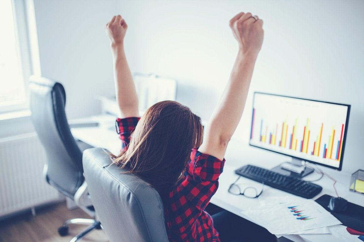 A woman sitting at a computer desk pumps her fists into the air.