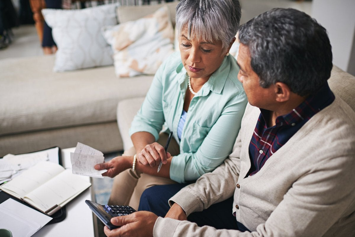 An older couple uses a laptop, calculator, and papers to budget while sitting on the living room sofa