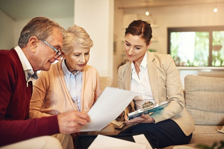 A mature couple discusses paperwork with a businesswoman in a home.