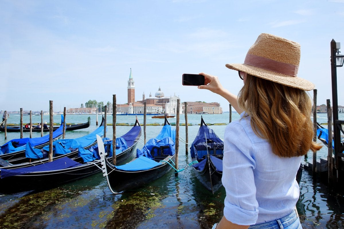 Woman in hat facing away and taking photos of an enormous old church across a bay.