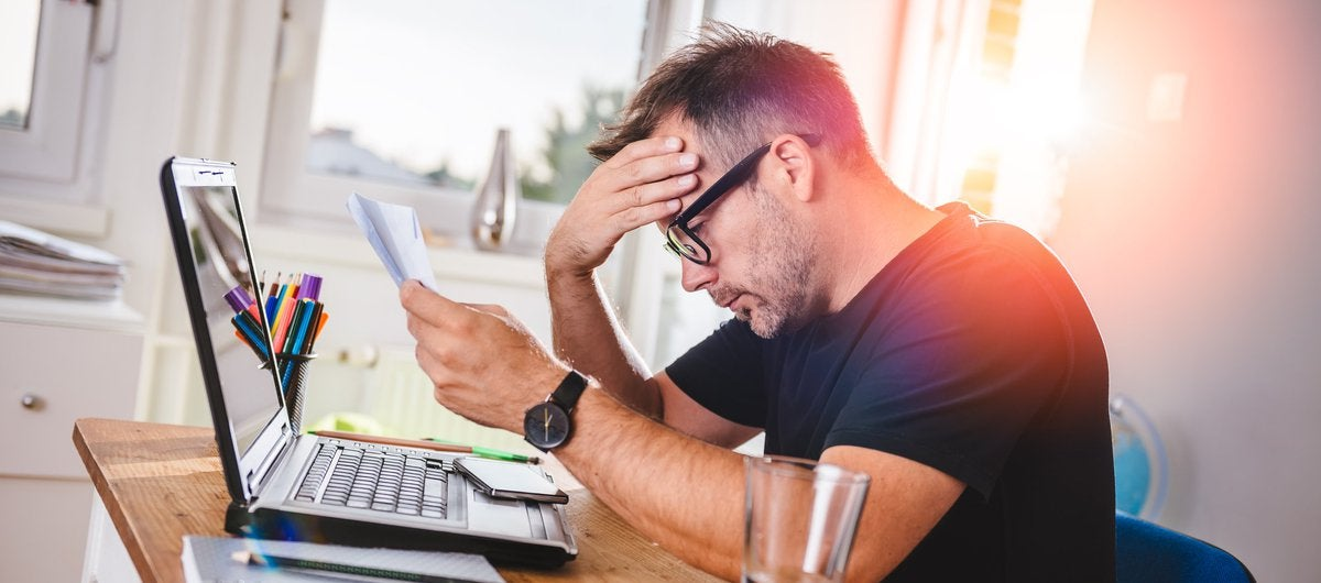 Stressed-out bespectacled man looking at document.