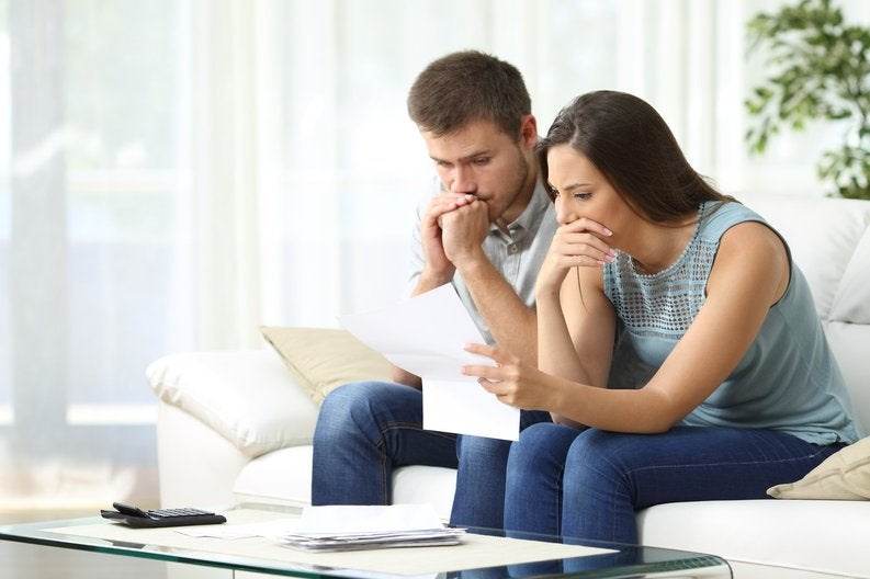 Man and woman sitting on couch looking worried with paperwork in hand
