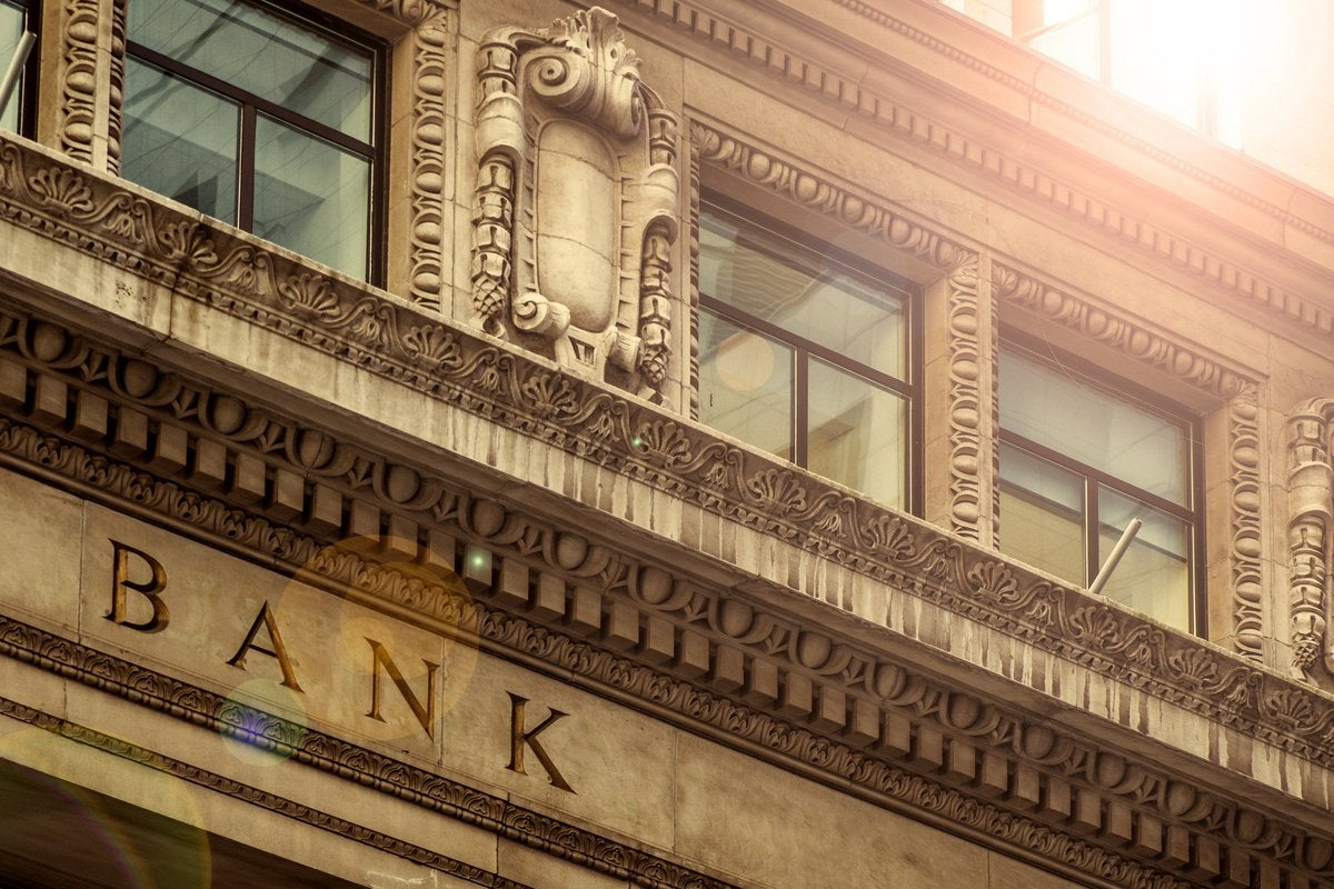 Sunlit facade of an archaic bank edifice.