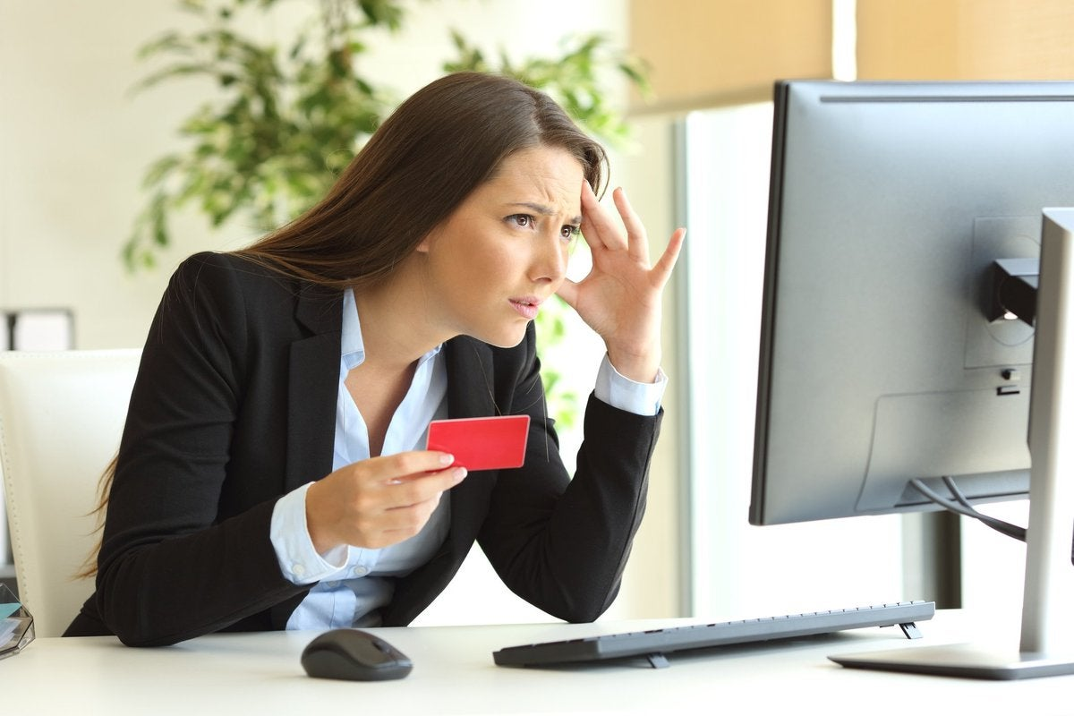 Frustrated woman holding credit card and looking at computer