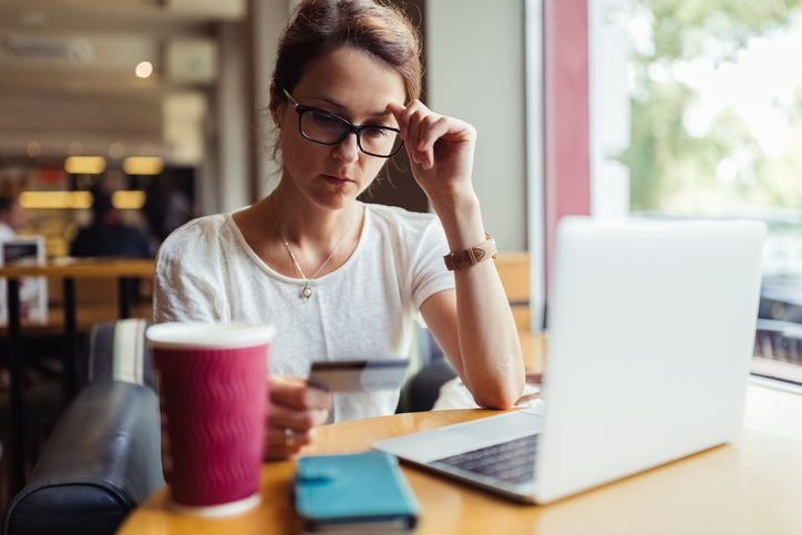 A woman looks at her credit card in confusion while sitting in a café.