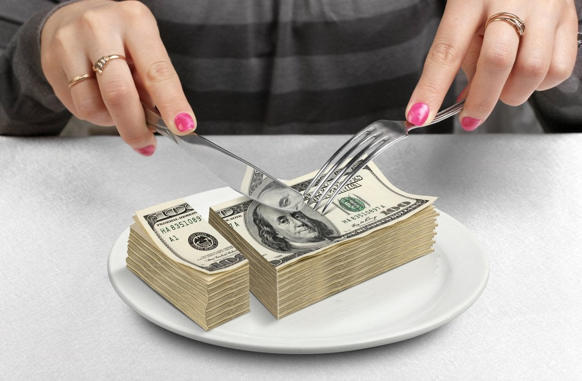 Pair of nail-polished hands cutting into a stack of 100-dollar bills with a fork and knife.