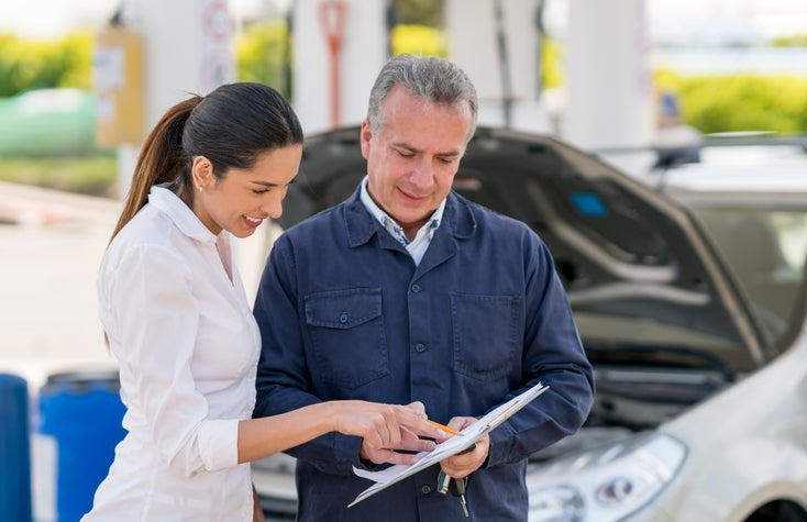 Young woman at a garage talking to a mechanic about her car. They both point at paperwork.