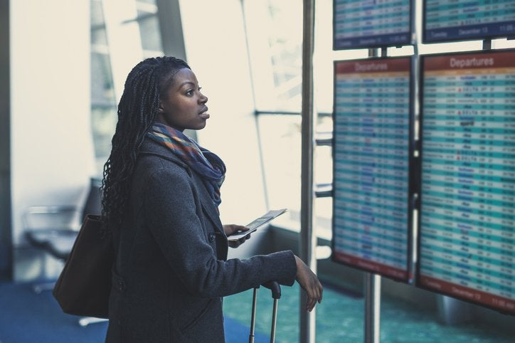 A woman at the airport checks the arrivals and departures board, holding her plane ticket and suitcase.