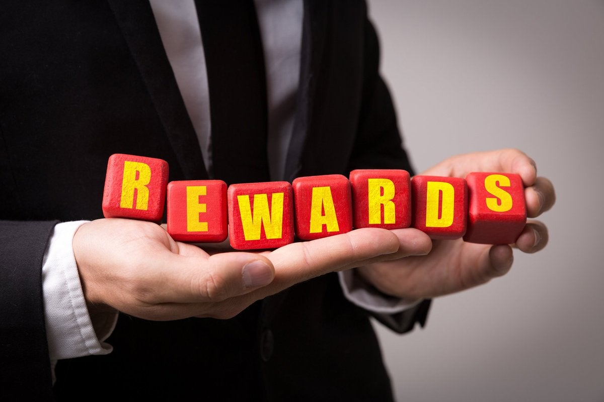 """Man in suit holding letter blocks that spell out """"rewards"""""""