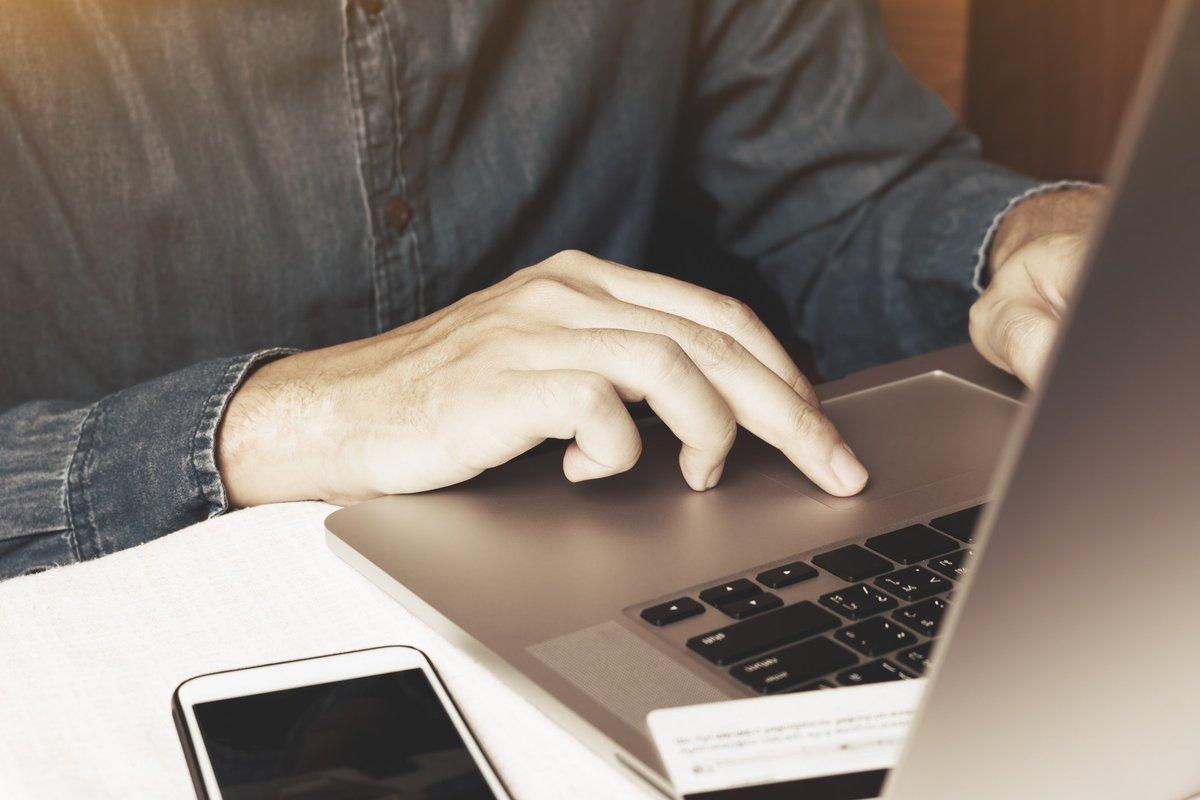 Man typing on laptop next to iPhone