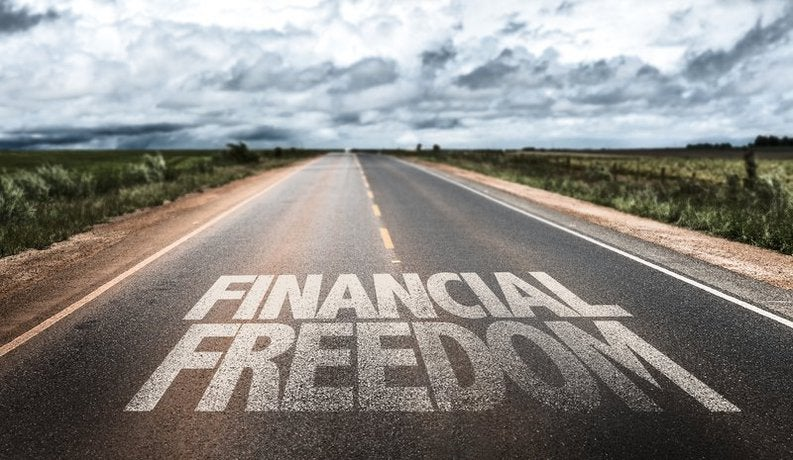 "Road with the words ""financial freedom"" painted on it"
