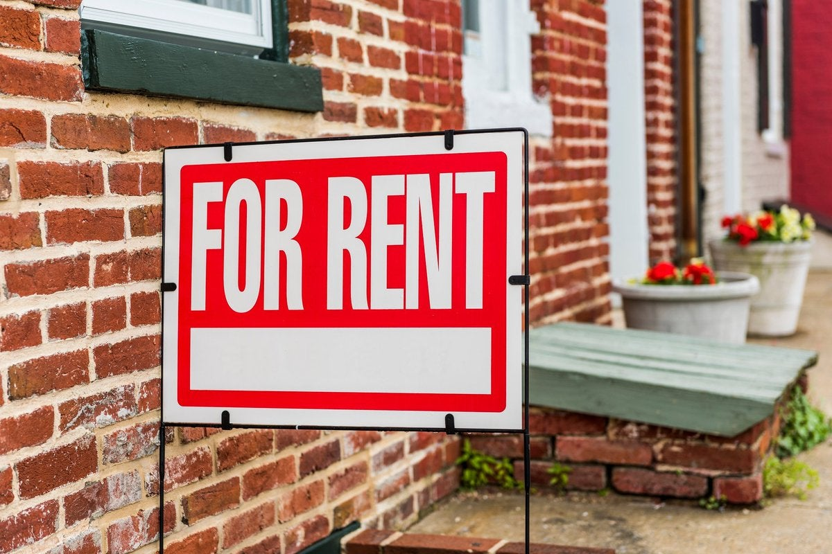 """""""for rent"""" sign outside of brick building"""