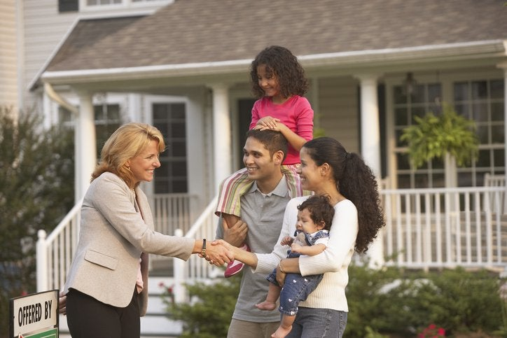 A family with children shakes hands with a real estate agent in front of a house.