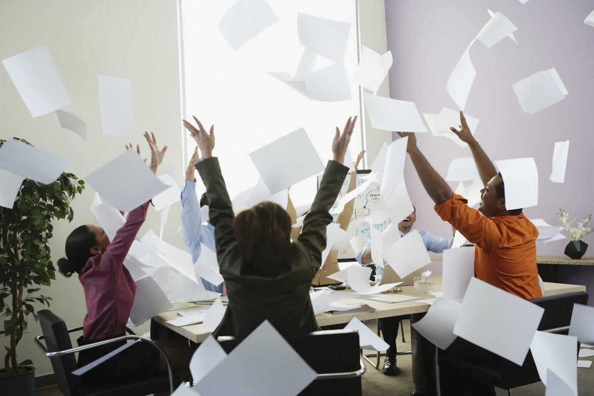 A group of office workers throw papers in the air excitedly.