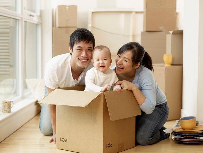 A couple smiles at a baby as they unpack moving boxes in their new home.