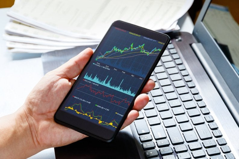 Hand holding a phone with stock charts on it over a laptop.