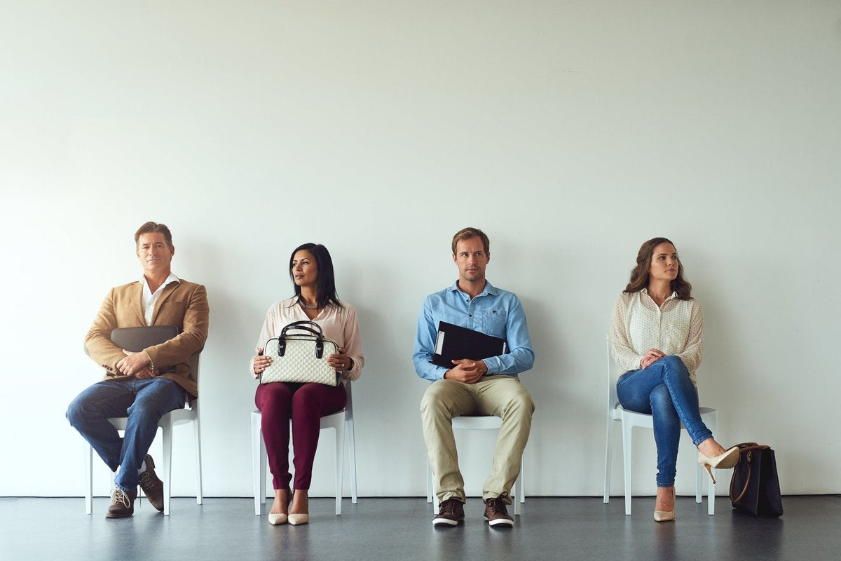 Four people in business attire sit waiting in an office.