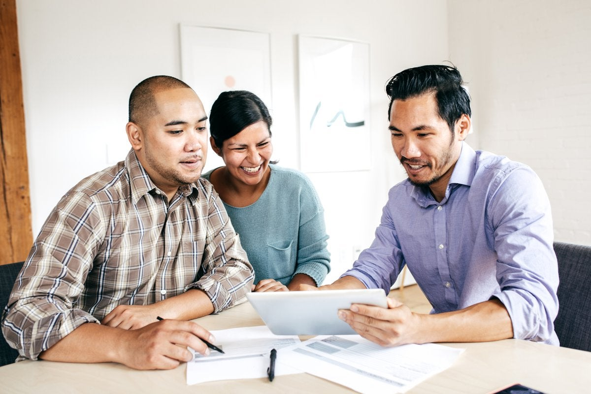 Three people smile as they look at paperwork in an office.