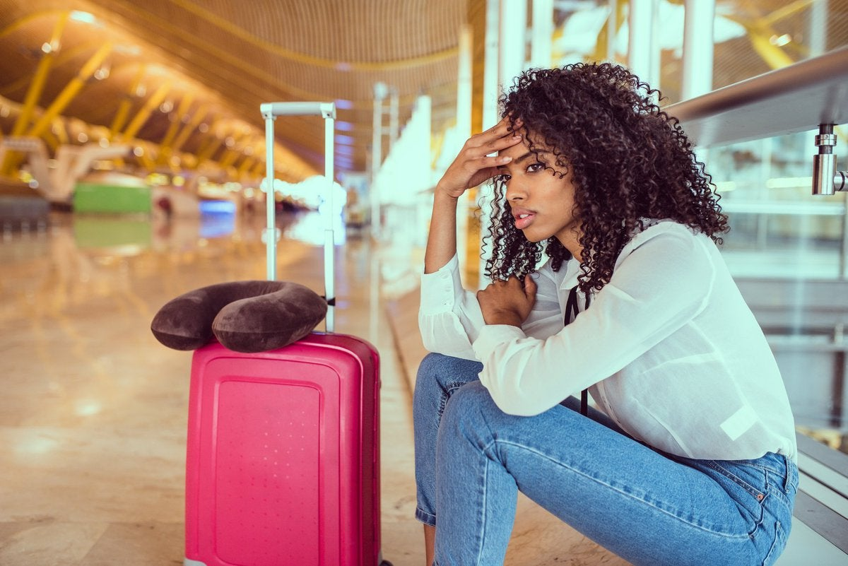 Woman sitting beside luggage at airport looking stressed.
