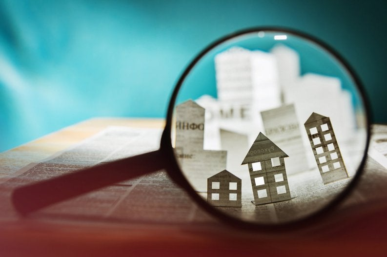 Magnifying glass over a paper house