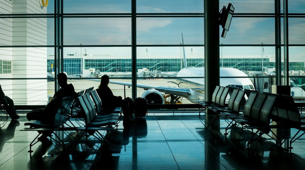People sitting in airport with plane outside window
