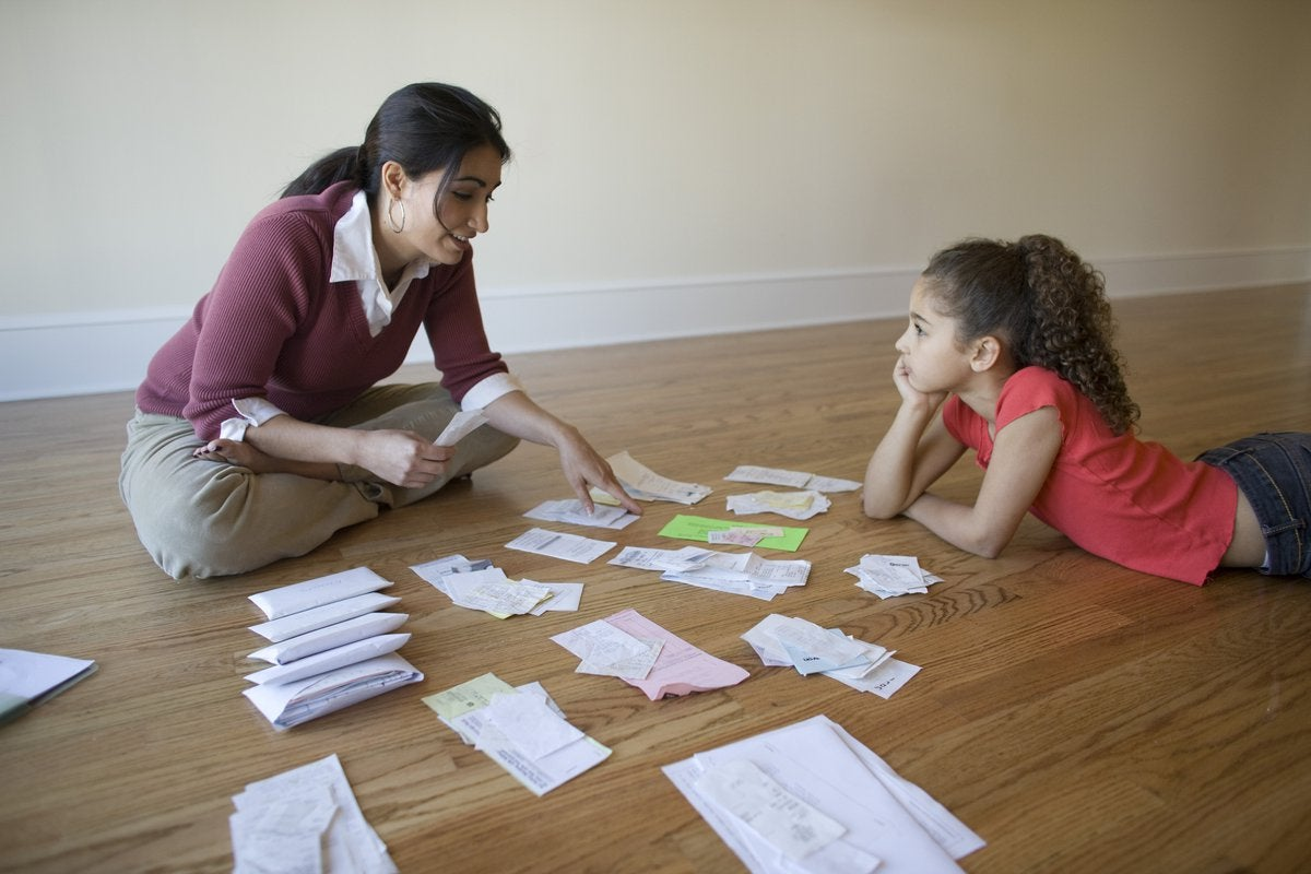 A parent and child sort through bills while sitting on the floor.
