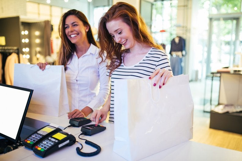 Two women paying with credit card at a store