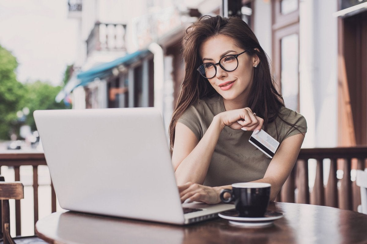 Woman sitting at outdoor cafe with laptop and credit card