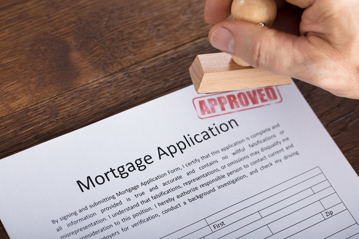 A mortgage application being marked with a stamp that says APPROVED