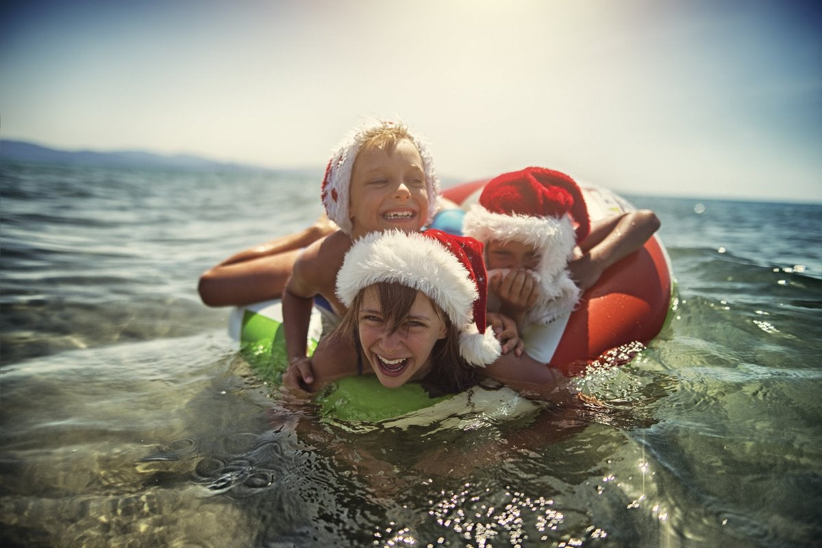 A woman and two children, all wearing Santa hats, swimming in the ocean together.