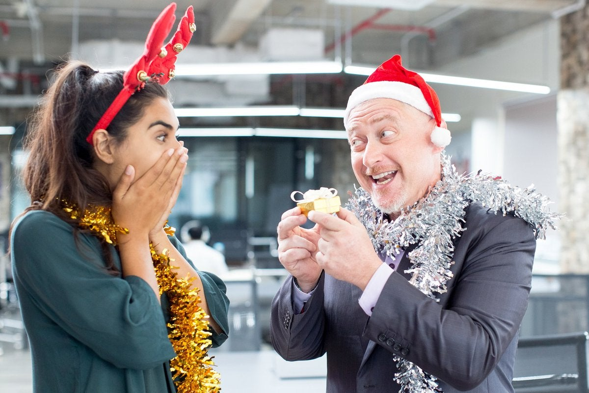 Middle-aged man in suit and Santa hat giving small gift-wrapped box to a young woman who is wearing fake reindeer antlers and looks overwhelmed with gratitude, all in an office.