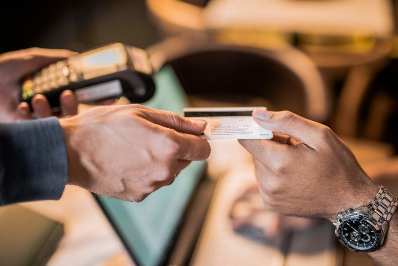 One hand passing a credit card to another hand.