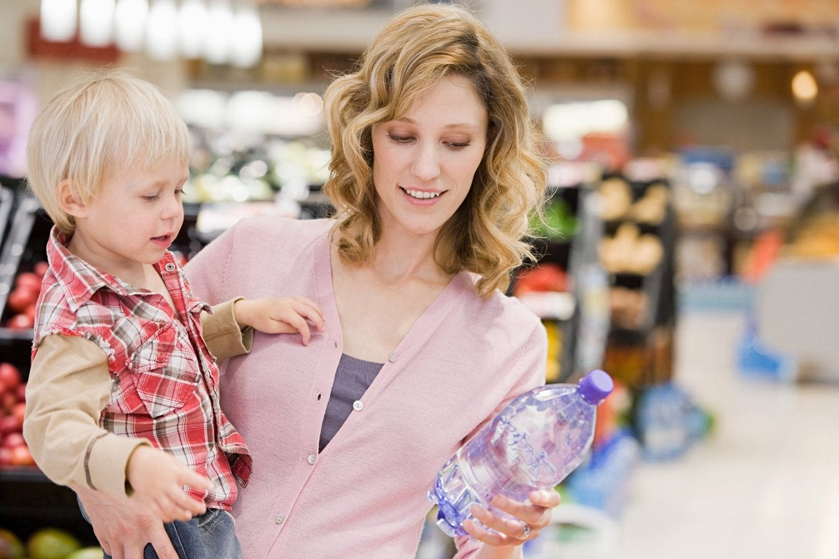 Woman holding toddler and looking at a bottle of water