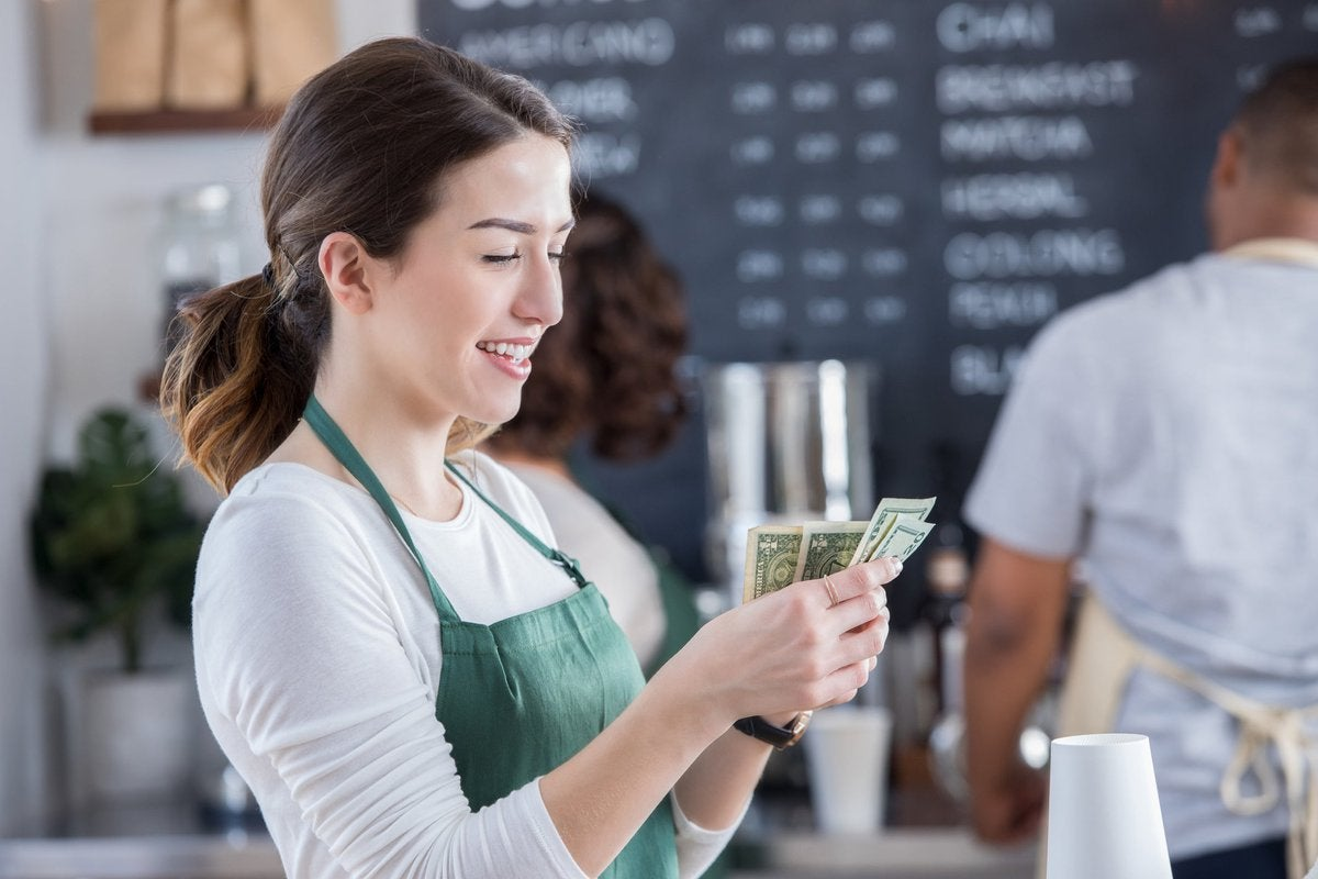 A smiling young barista counts cash in coffee shop.