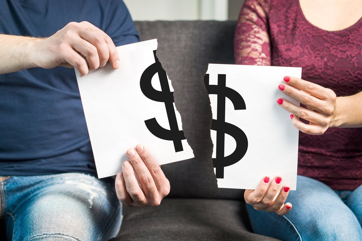 A couple sitting on a couch ripping apart a piece of paper with a big black dollar sign printed on it.