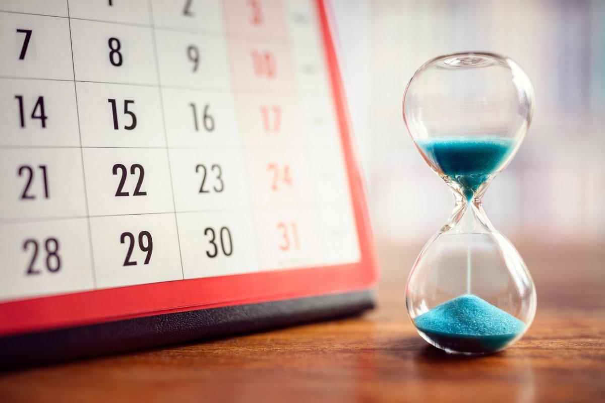 Hourglass full of blue sand next to a calendar