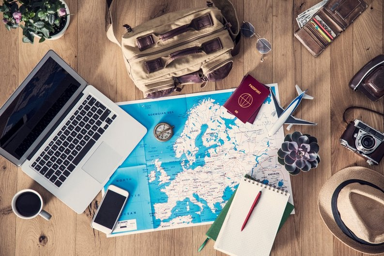 Map of Europe with laptop, phone, passport, and notebook