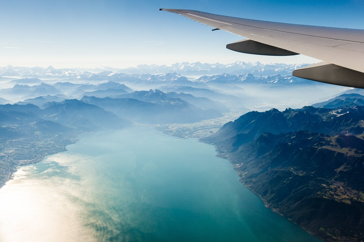 Airplane wing flying over mountains and lakes