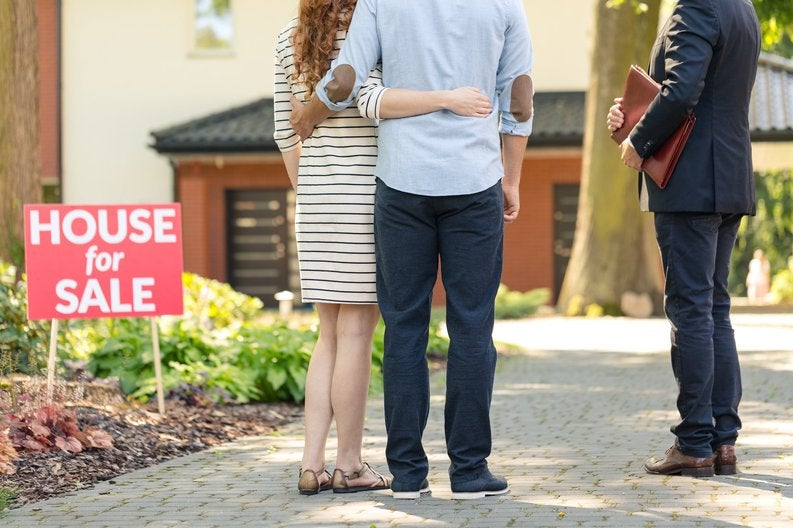 Couple with real estate agent at a house for sale