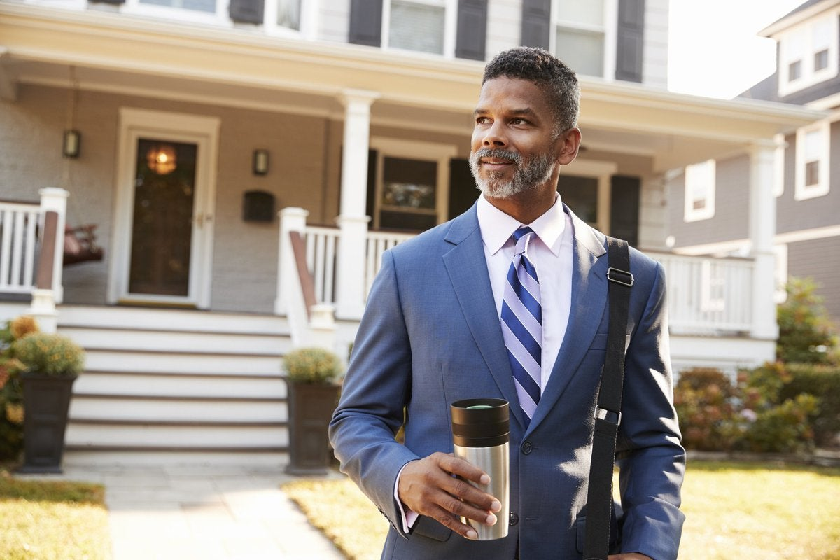 Middle-aged man in suit confidently leaving his enormous house in the morning.