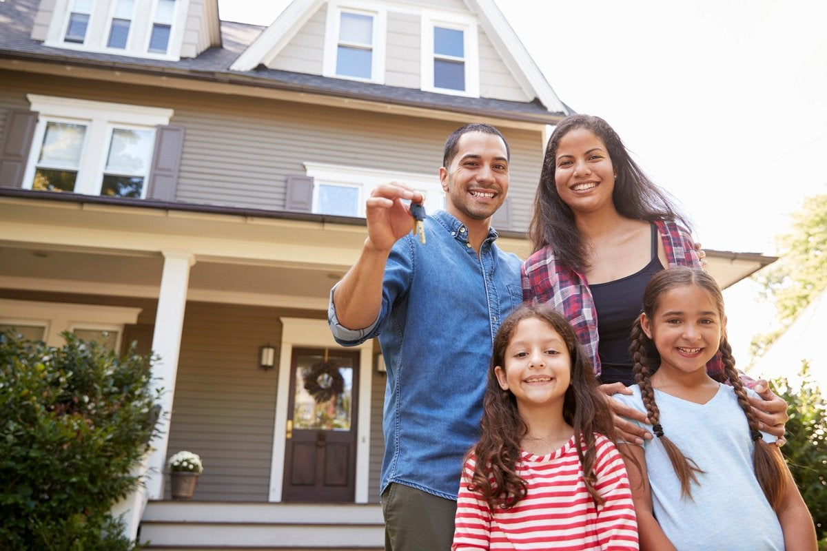 A husband, wife, and two daughters stand outside a home holding house keys.