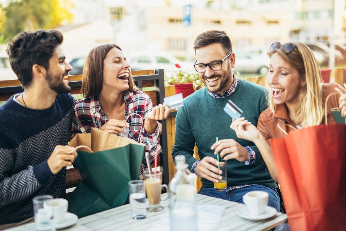 Group of young men and women laughing at table holding credit cards