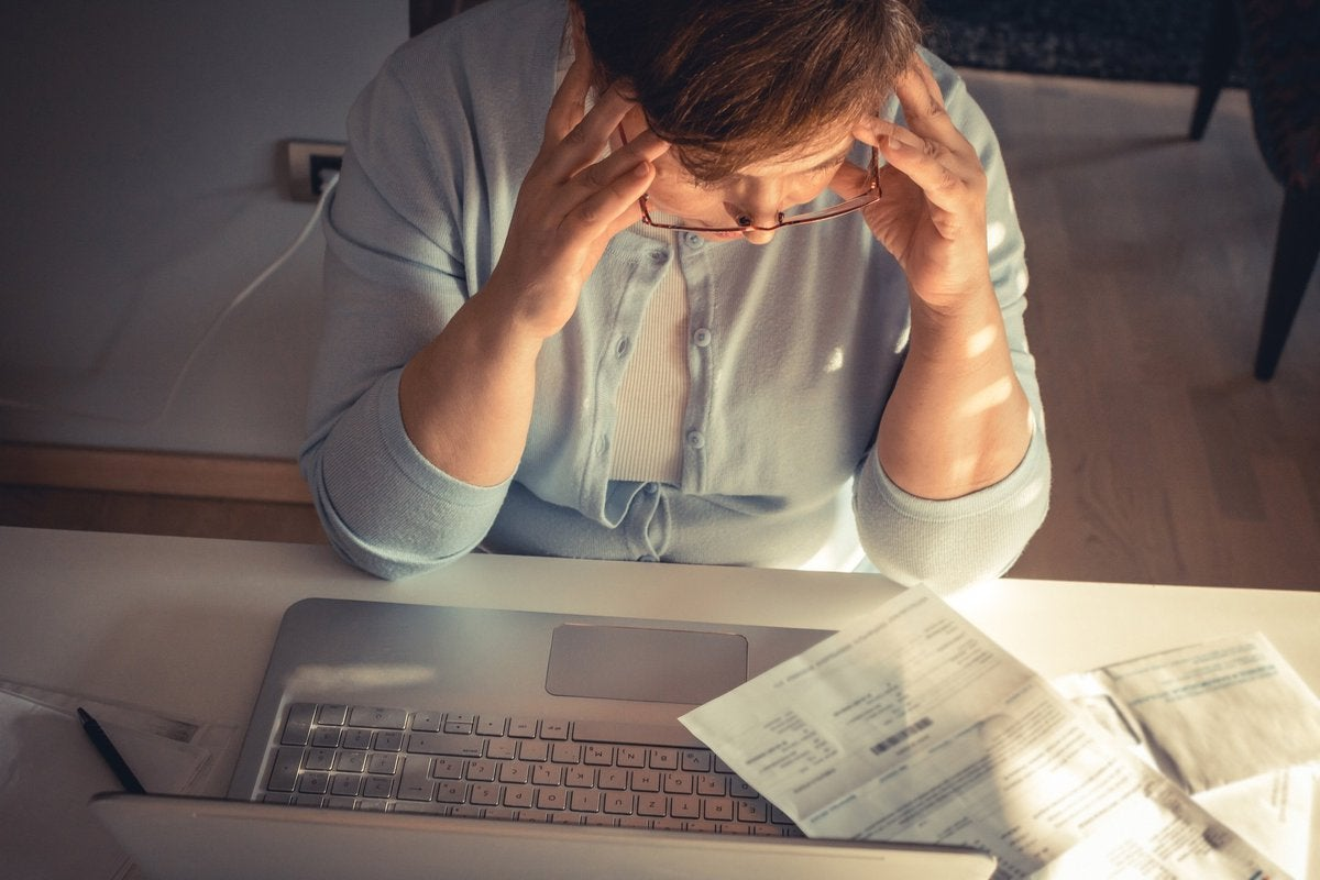 Person stressed out at computer looking at bills