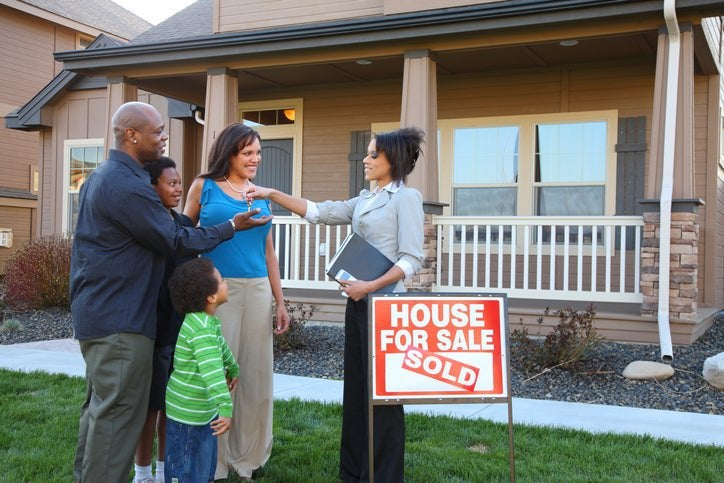 Family takes house keys from a real estate agent in front of house they just bought