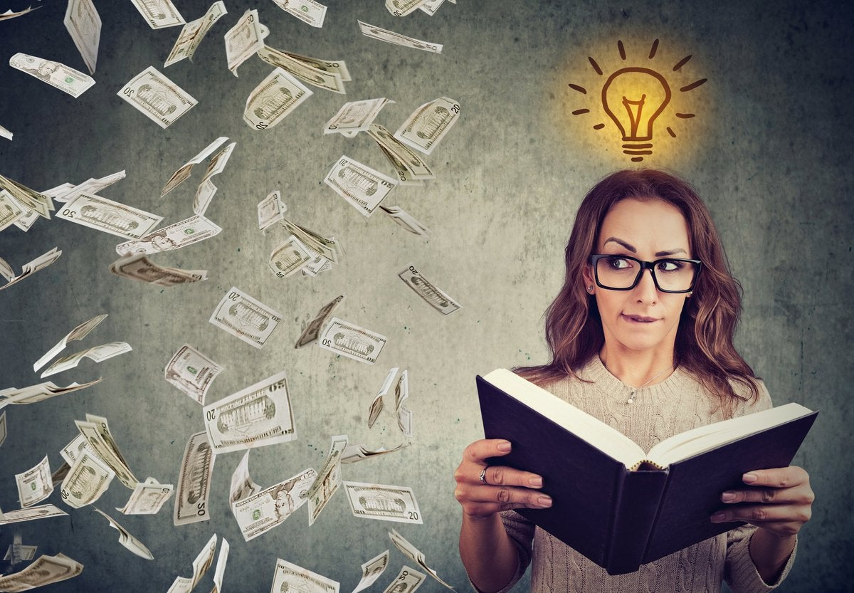 Bespectacled woman opening book and looking over at raining money.
