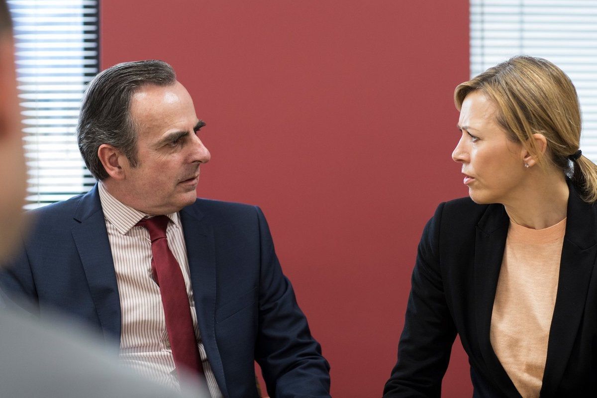 Man and woman looking confrontational in a boardroom.