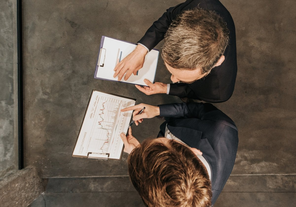 High angle view of two business workers cooperating while working on bitcoin development diagram in the office.