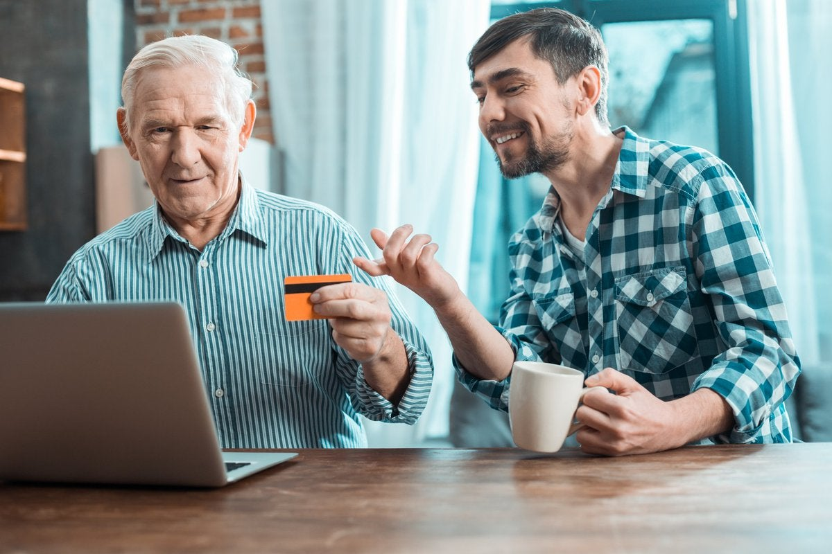 Baby boomer holding credit card beside smiling millennial.