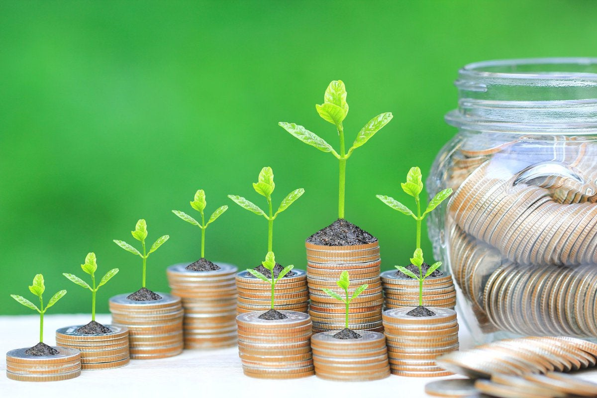 Tiny sprouts growing out of coin stacks of varying heights beside a jar full of coins.