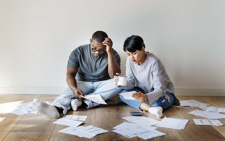 A couple sit on the floor in a room with no furniture surrounded by paperwork and bills.
